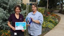 Recreation Officer Lynda White and ADirector of Nursing Michelle Crawford proudly display their gardening competition trophy in the prize winning gardens at Oakey Hospital