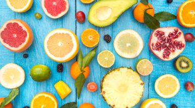 An array of cut fruits laid out on a blue table.>