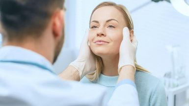 A woman gets a facial surgery consultation by a surgeon