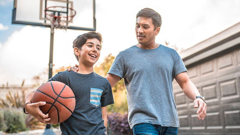 Father and son chatting on a basketball court