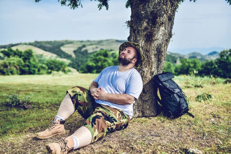 A man lies back against a tree after a hike.