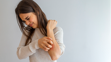A woman with eczema scratches her itchy elbow with a pained expression