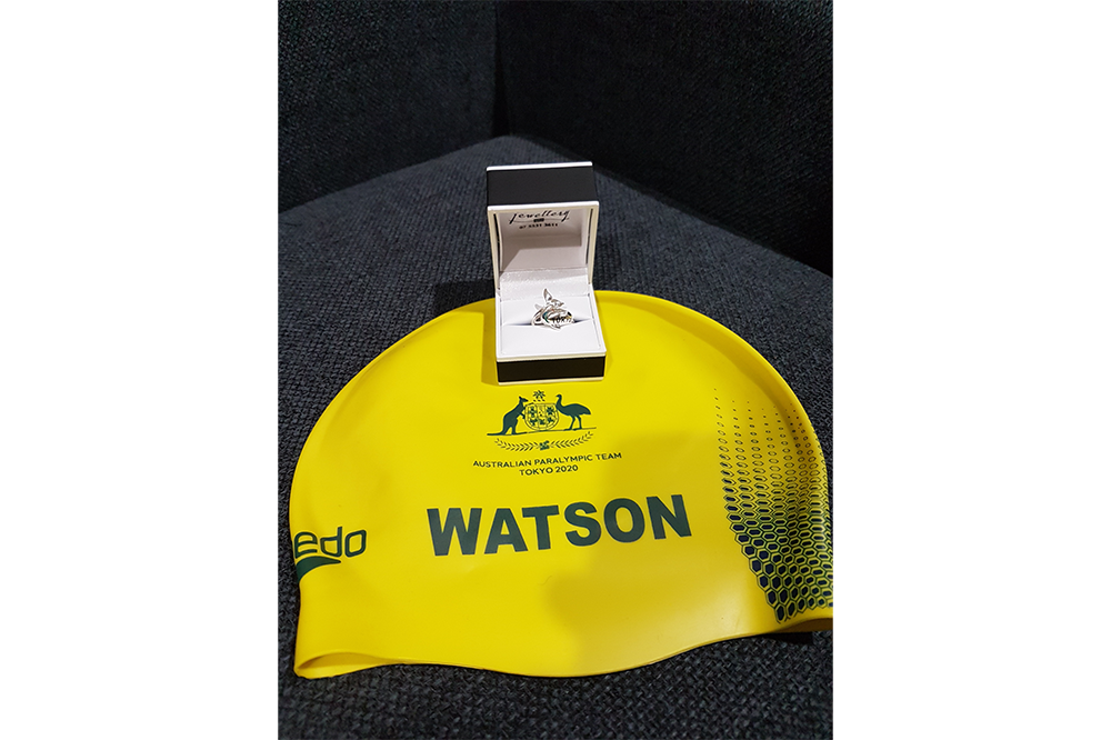 Yellow Olympic swimming cap reading 'Watson' and Olympic ring displayed in a box