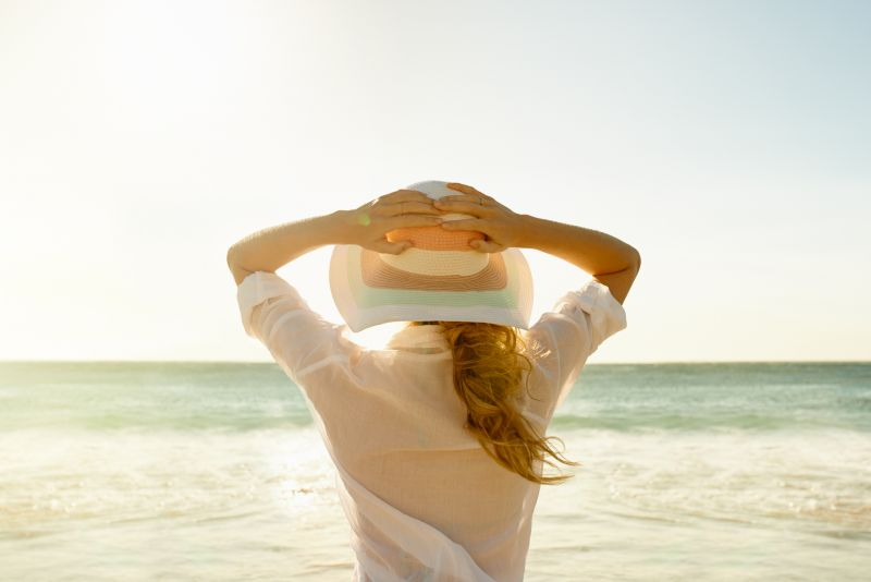 A woman stands facing the beach wearing a long-sleeved cotton button up shirt and a large hat.