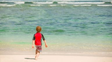 young boy wearing a red rash vest having fun on a tropical beach