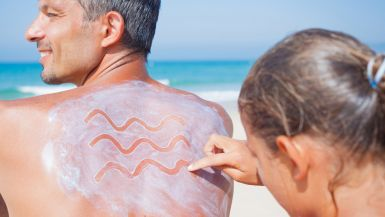 A father sits at the beach with his back to the camera, while his daughter applies sunscreen to his back. >