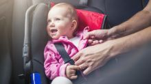 A parent straps a baby into a car seat