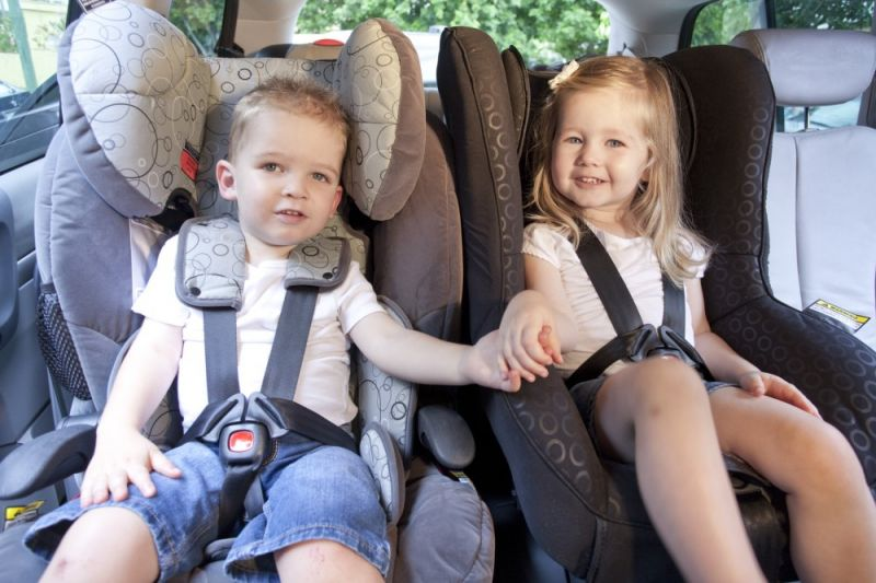 A boy and a girl sitting side by side in two child car restraints holding hands