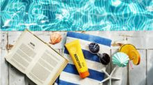 On the edge of a pool sit a towel, book, sunglasses and a tube of SPF 50+ sunscreen.