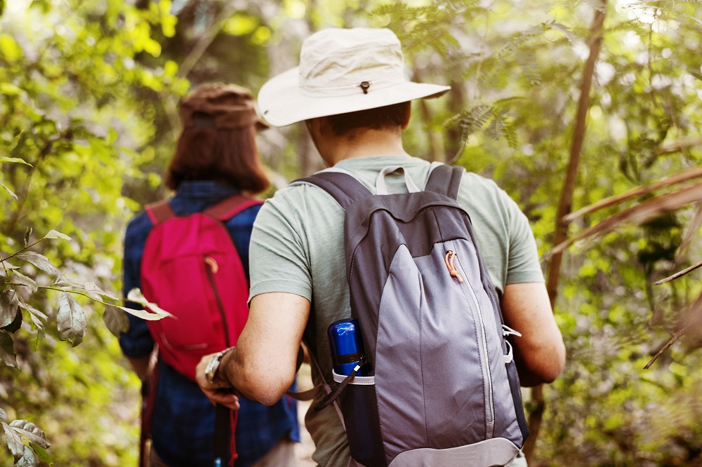 A man and woman walk through the bush on an orienteering challenge.