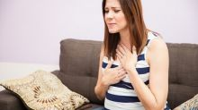 Pregnant woman experiencing heartburn