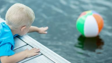 Boy reaching for beach ball in the water