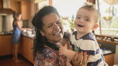 An older woman holds a young boy, both are smiling at the camera.