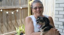 Sandra sits in her backyard holding her dog.