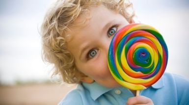 A little boy holds a large rainbow lollipop in front of his face, peeking out with eyes wide from behind it.