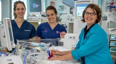 NICU Nurses next to crib