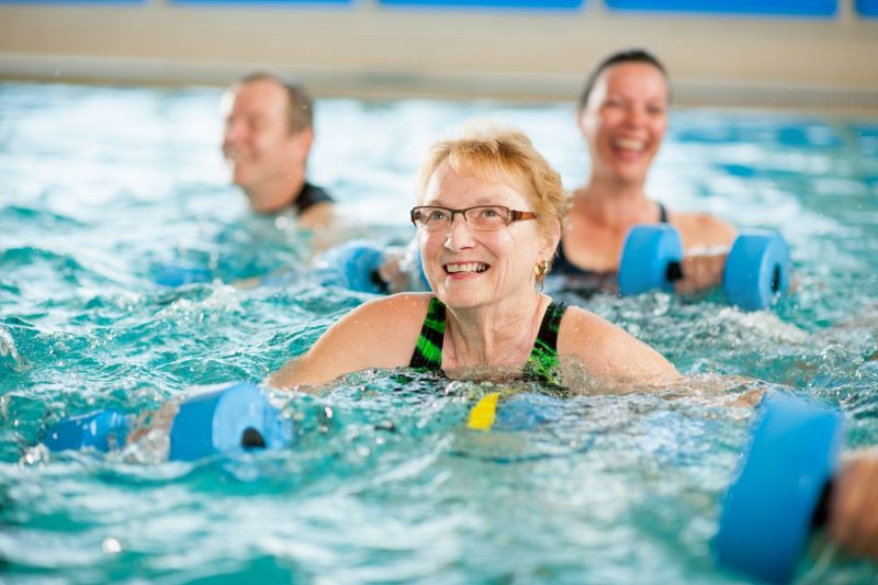 An older woman smiles as she takes part in an aqua aerobics class