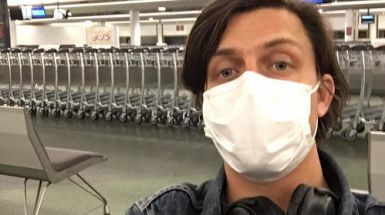 Ben stands in an empty airport wearing a mask