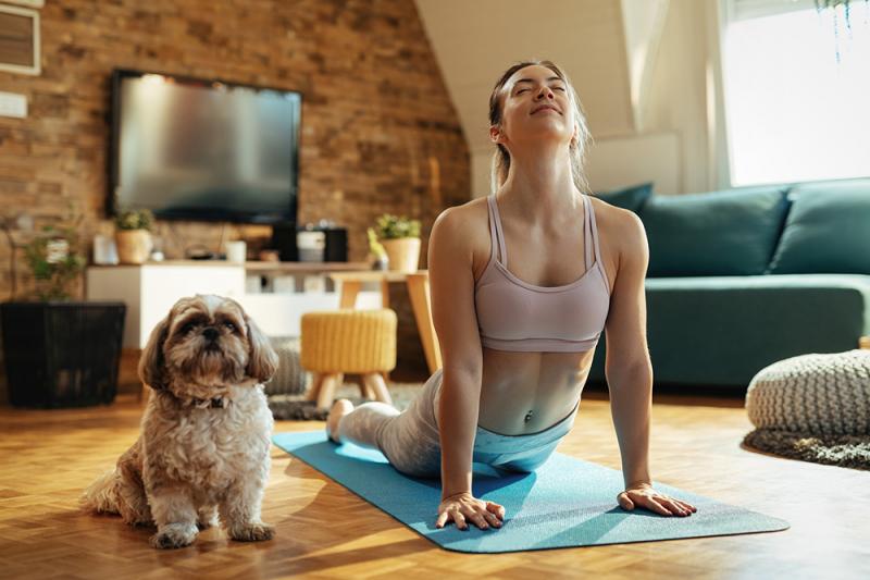 A woman and cute fluffy dog do yoga's cobra pose