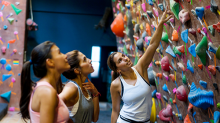 Three young woman looking at the routes on an indoor rock climbing wall