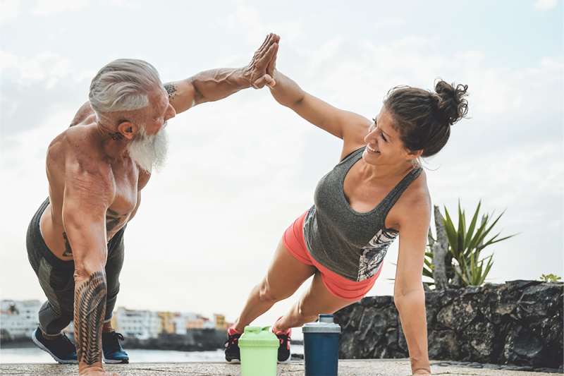 An older man and woman doing push ups together