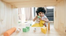 A young boy plays with blocks inside a wooden box.