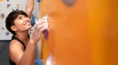 A young woman smiles as she holds on to two handles on a climbing wall.
