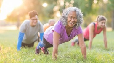 A group of older people do group exercise in the park