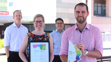 Four members of the pharmacy team stand in front of the Redcliffe Hospital. Two are holding an award the team received.