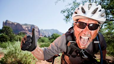 An excited mature male mountain biker gives a thumbs up