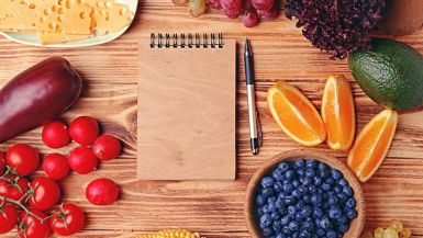 A notepad and pen on a wooden table, amid a variety of fruit and vegetables