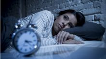 A woman lies awake in bed, looking upset, as her clock ticks past 3am.