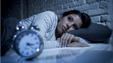 A woman lies awake in bed, looking upset, as her clock ticks past 3am.>