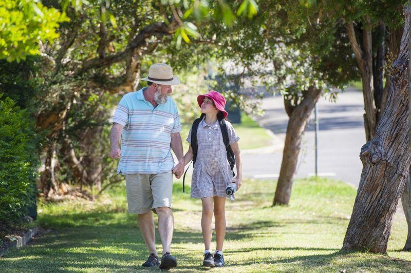 Grandfather walks young girl to school