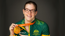 Paralympian athlete in yellow and green Olympic uniform pointing at gold medal