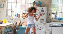 A woman dances in her kitchen after waking up.