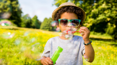 Young boy blowing bubbles outside