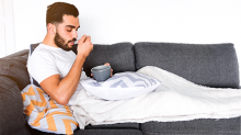 Young man wrapped in a blanket eating soup on the couch
