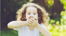 A little girl stands in the garden, hands over her mouth like she feels she might be about to be sick.