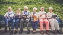 6 elderly men and women sit on a park bench, reading, knitting, using phones and tablets.