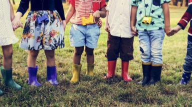 A group of children stand outside wearing gumboots and holding hands.