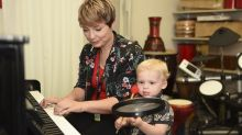 Woman plays piano with child