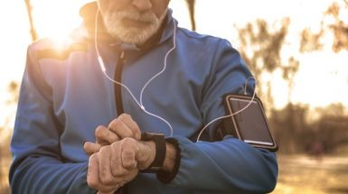 An older man in exercise gear programs his watch before a run.