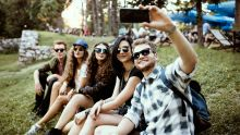 Five friends seated in a row on a hill, wearing sunglasses and taking a selfie