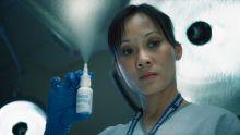 A nurse squeezes a nasal spray bottle