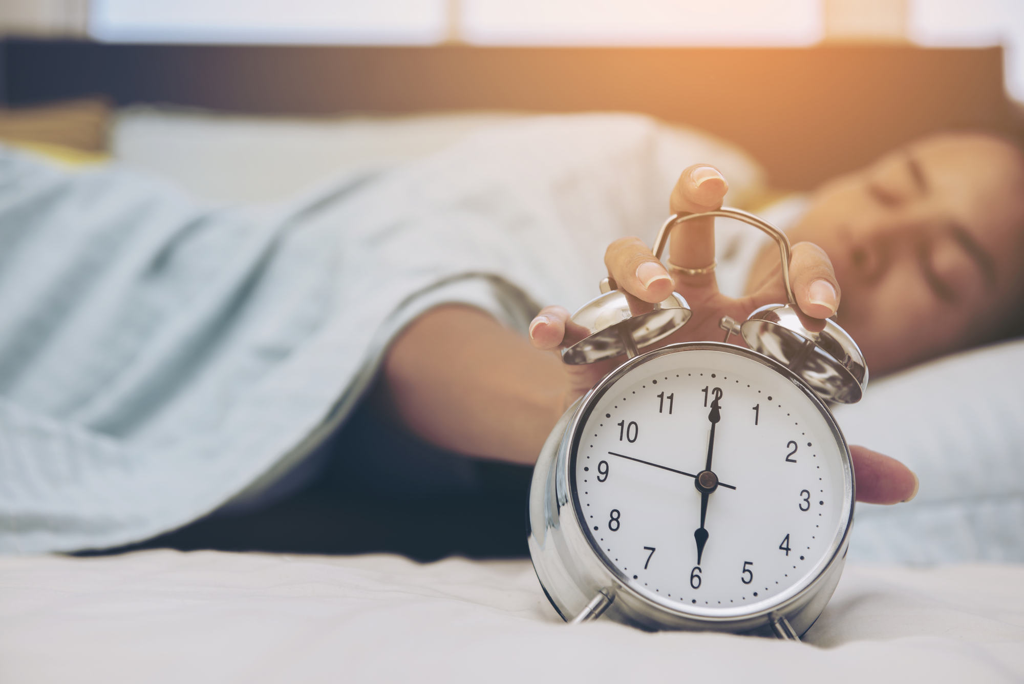 A man lies in bed a presses snooze on his alarm clock.