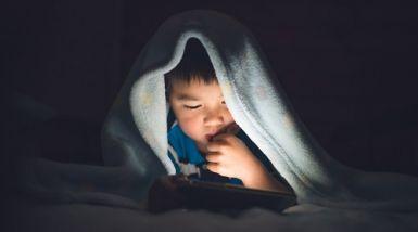 Little boy lies under blanket with phone.