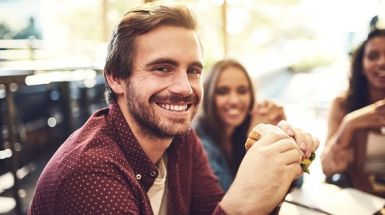 Man smiles and eats a wholegrain sandwich at a cafe with friends