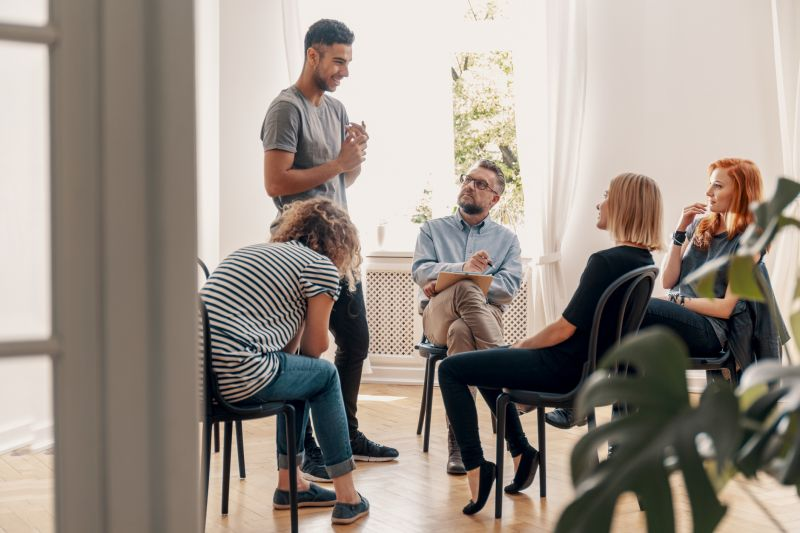 A young man stands and shares his experience in a group therapy session