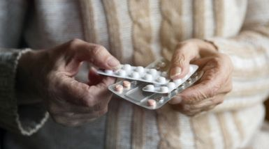 The hands of an elderly woman are shown, holding a generic packet of medicine pills.